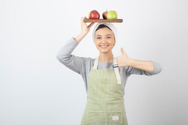 Lachende vrouwelijke kok bedrijf plaat van appels op wit.
