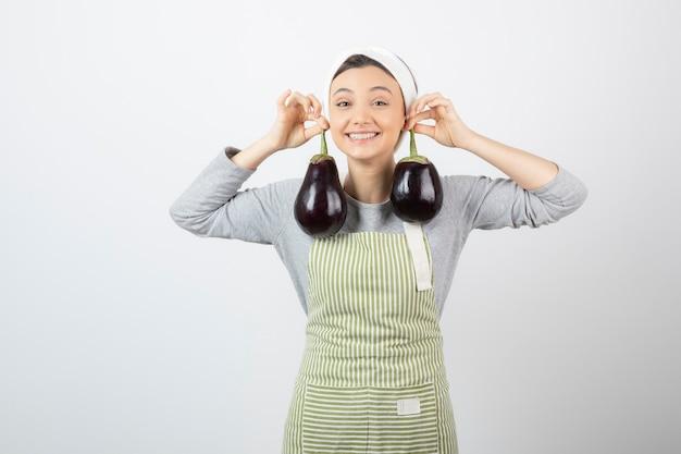 Lachende vrouwelijke kok poseren met grote aubergines op wit.
