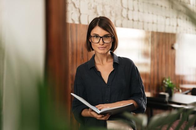Lachende vrouwelijke manager in brillen met documenten in handen