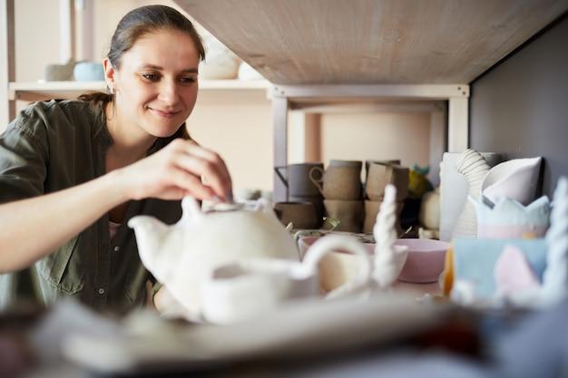 Lachende vrouwelijke potter in opslagruimte