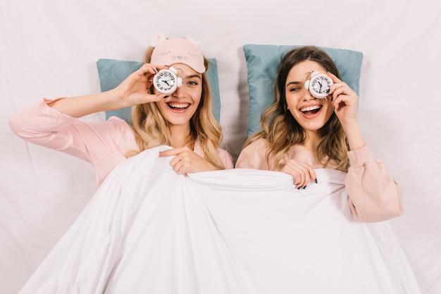 Lachende vrouwen die in bed rommelen