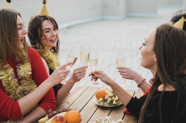 Lachende vrouwen die omhoog glazen champagne toejuichen