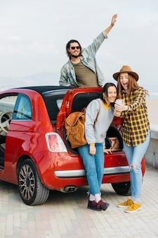 Lachende vrouwen die selfie op smartphone dichtbij autoboomstam en mens nemen die uit auto leunen