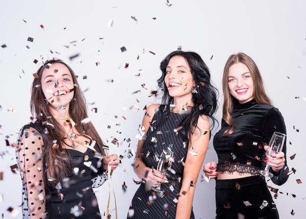 Lachende vrouwen in avonddoeken met glazen tussen het werpen van confettien