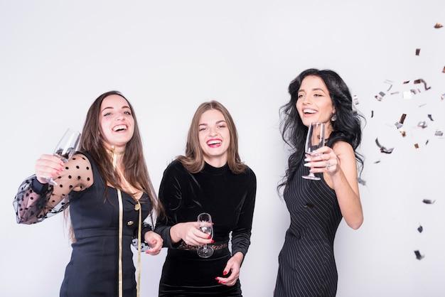 Lachende vrouwen in avondkleding met een bril in de buurt van confetti