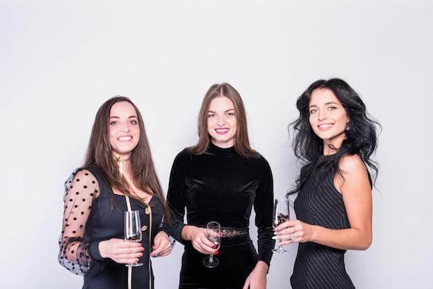 Lachende vrouwen in avondkleding met een bril