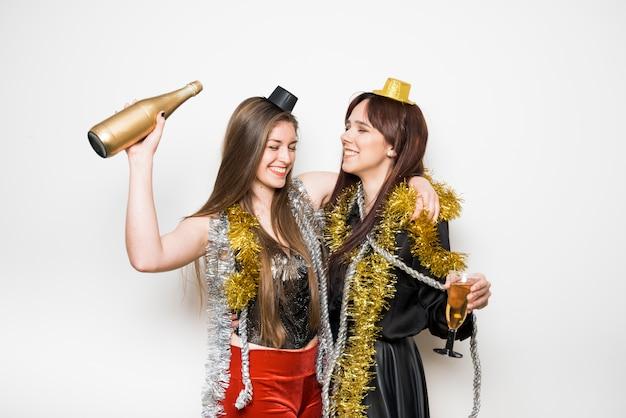 Lachende vrouwen in avondkleding met een glas drank en een fles