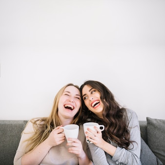 Lachende vrouwen met mokken