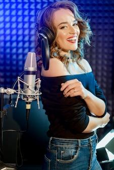 Lachende vrouwenzanger met hoofdtelefoons dichtbij de microfoon met een uitdrukking van geluk