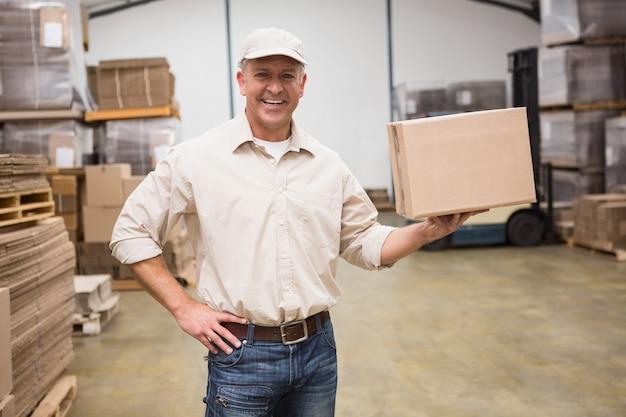 Lachende werknemer met kartonnen doos