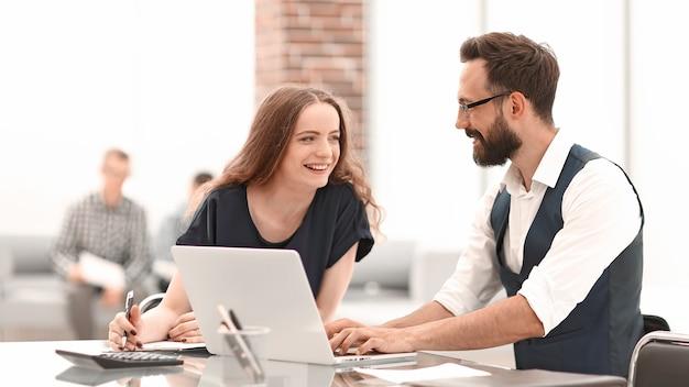 Lachende werknemers van het bedrijf bespreken iets zittend aan de desk.office weekdagen