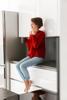 Lachende youthfull vrouw draagt ?? trui zittend op een keukentafel thuis, met behulp van mobiele telefoon