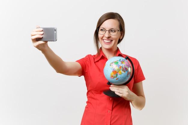 Lachende zakelijke leraar vrouw in rood shirt met mobiele telefoon en doen selfie schot met globe geïsoleerd op een witte achtergrond. onderwijs onderwijzen in het concept van de middelbare school universiteit. ruimte kopiëren.