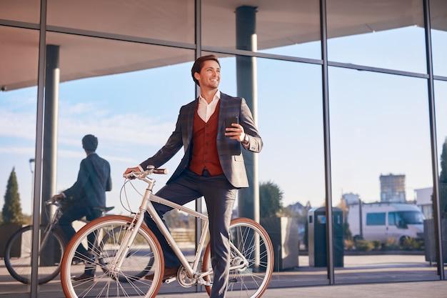Lachende zakenman met telefoon en fiets op stadsstraat