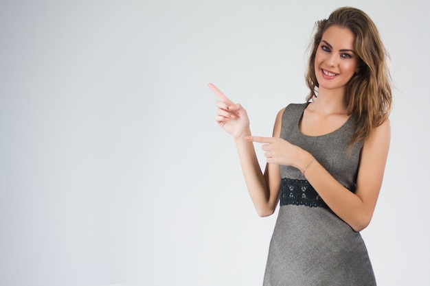 Lachende zakenvrouw wijst vinger op exemplaar ruimte. geïsoleerde portret