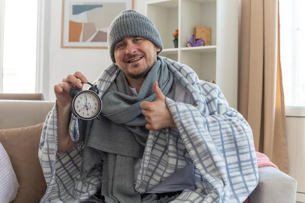 Lachende zieke man met sjaal om nek met wintermuts gewikkeld in plaid met wekker en duimen omhoog zittend op de bank in de woonkamer