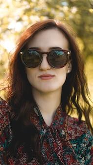 Lachende zomer vrouw met zonnebril. mooie jonge vrouw buiten. geniet van de natuur. gezond lachend meisje in het voorjaarspark. zonnige dag