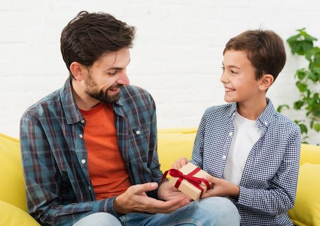 Lachende zoon biedt een geschenk aan zijn vader