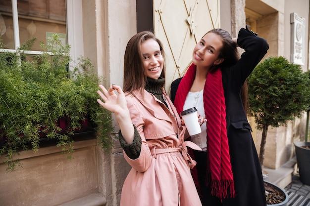 Lachende zusters in jassen op straat
