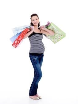 Lachende zwangere vrouw met boodschappentassen