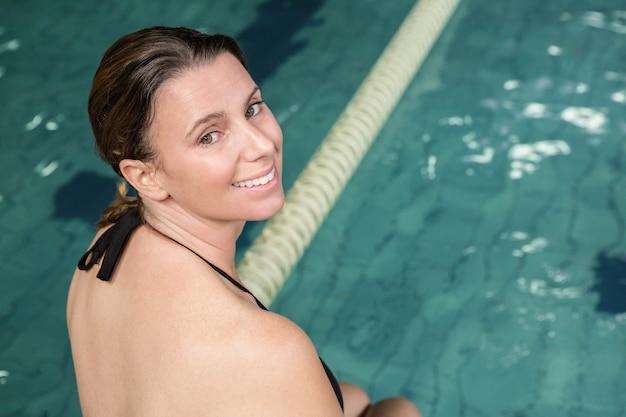 Lachende zwangere vrouw zittend op de rand van het zwembad en kijken terug naar de camera