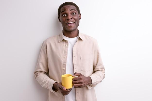 Lachende zwarte man met een kopje koffie in de ochtend