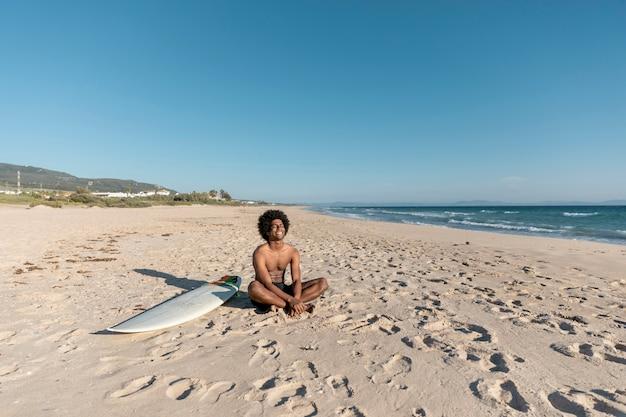 Lachende zwarte man ontspannen op het strand