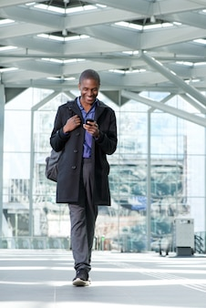 Lachende zwarte zakenman lopen met mobiele telefoon op de luchthaven