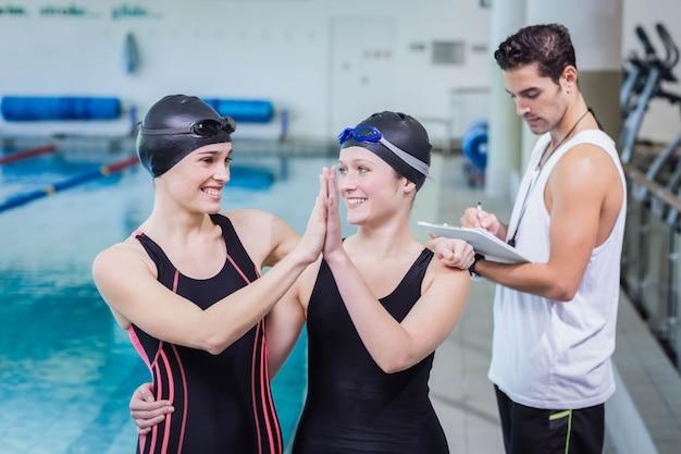 Lachende zwemmers hoge fiving in het recreatiecentrum