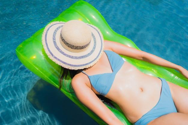 Lacht de gelukkige glimlach van de portret mooie jonge aziatische vrouw en vrije tijd in het zwembad ontspannen