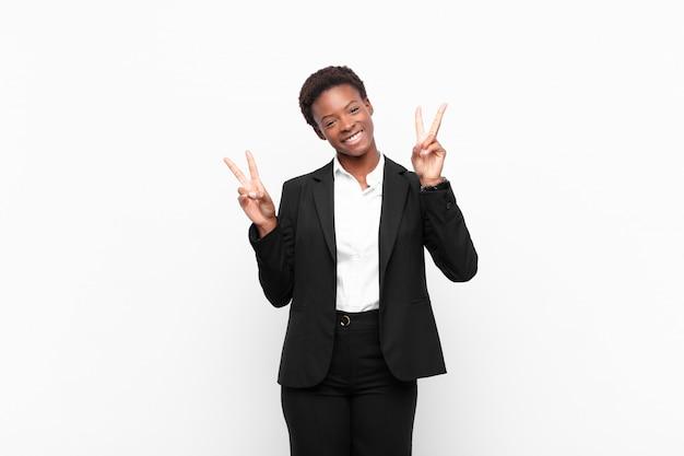 Lacht en kijkt gelukkig, vriendelijk en tevreden, gebaart overwinning of vrede met beide handen