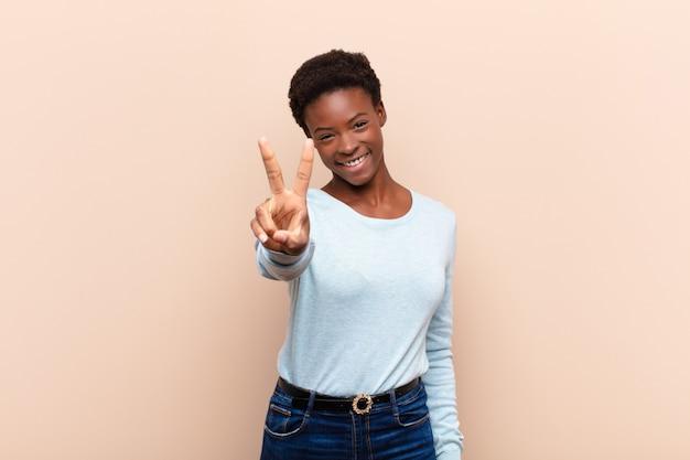 Lacht en kijkt gelukkig, zorgeloos en positief, gebaart overwinning of vrede met één hand