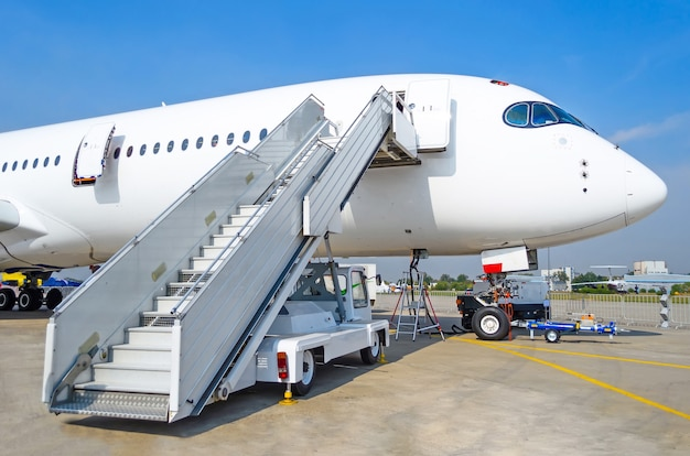 Ladder naar de ingang van het vliegtuig op de parkeerplaats op de luchthaven, bekijk de neus van het vliegtuig.