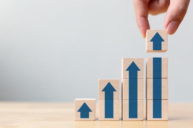 Laddercarrièrepad voor het concept van het proces van het de bedrijfsgroei succesproces. hand die houtsnedestapel stapelen als stappentrede met omhoog pijl