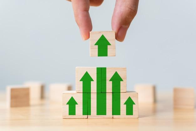 Laddercarrièrepad voor zakelijk groeisuccesproces stapelen van houtblokken als staptrap met pijl omhoog. hand die houten kubusblok op hoogste piramide zet