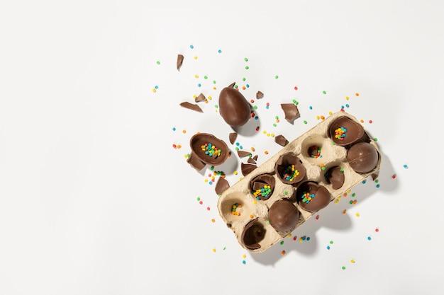 Lade met gebroken chocolade paaseieren en veelkleurige zoete snoep versieringen op een licht
