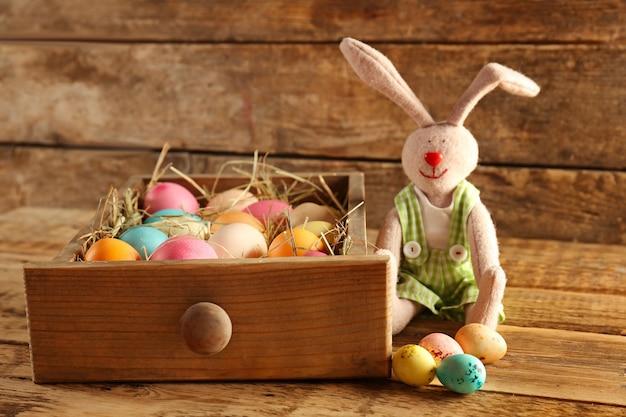 Lade met kleurrijke eieren en paashaas op houten tafel