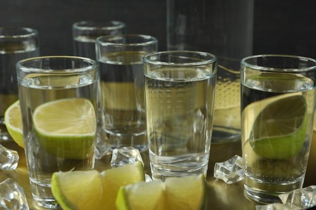 Lade met shots en fles wodka, limoen en ijs, close-up