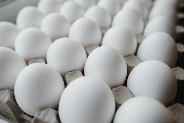 Lade met witte verse eieren close-up op een karton