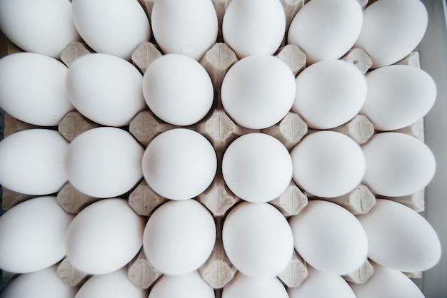 Lade met witte verse eieren close-up op een kartonnen vorm. agrarische industrie.