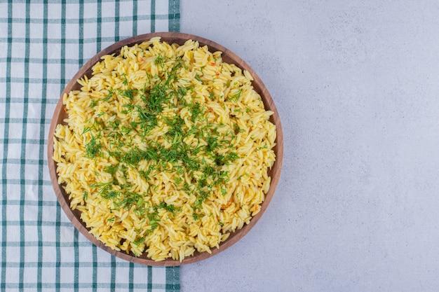 Lade van gekookte bruine rijst gegarneerd met dille op marmeren achtergrond.