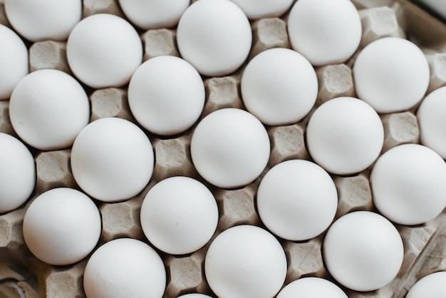 Lade van witte verse eieren close-up op een kartonnen vorm. agrarische industrie