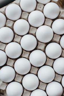 Lade van witte verse eieren close-up op een kartonnen vorm. agrarische industrie.