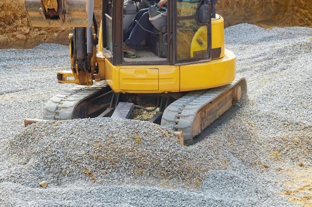 Laden van stenen graafmachine werkt in grindgroeve