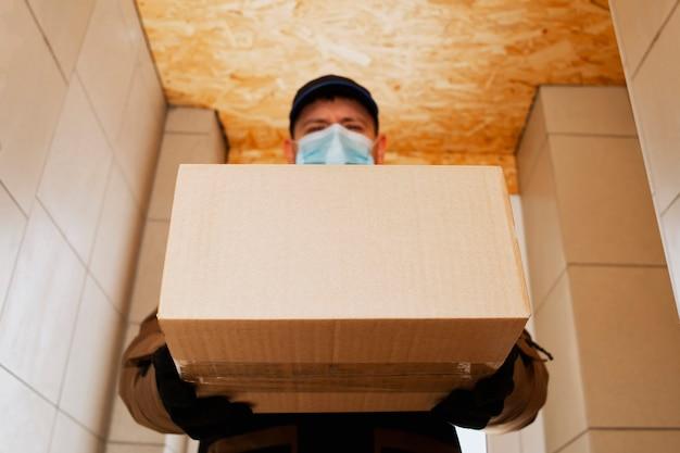 Lader bezorger jonge man met masker brengt een kartonnen doos het huis in.