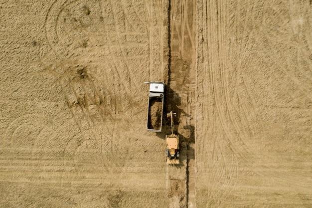 Lader graafmachine laadt de grond in de vrachtwagen bij de wegenbouw