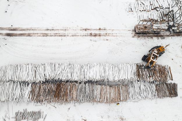 Lader laadt logboeken gestapeld in stapels bedekt met sneeuw