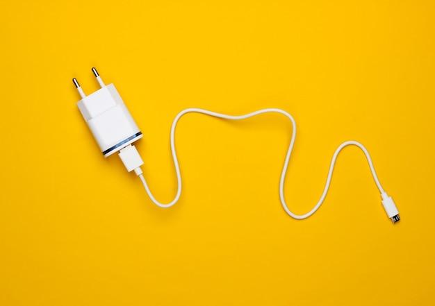 Lader met kabel op gele achtergrond. bovenaanzicht