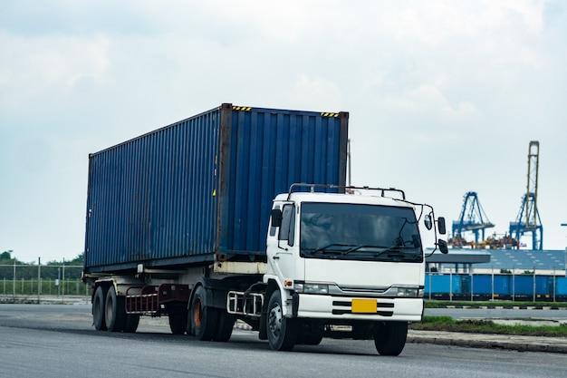 Lading blauwe containervrachtwagen in scheepshaven logistiek. transportindustrie in havenbedrijf. import, export logistiek industrieel