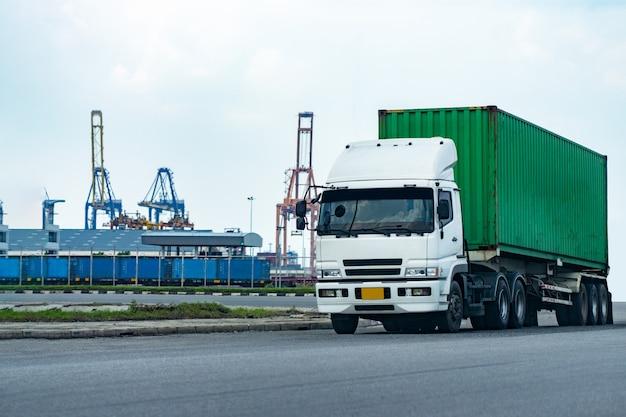 Lading groene containervrachtwagen in scheepshaven logistiek. transportindustrie in haven bedrijfsconcept.